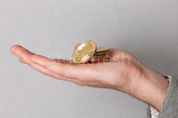 Close up of man showing stack of golden bitcoins Stock photo © deandrobot