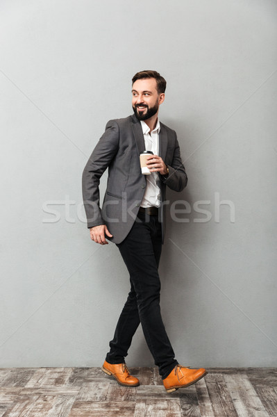 Full-length image of happy man with takeaway coffee smiling, and Stock photo © deandrobot