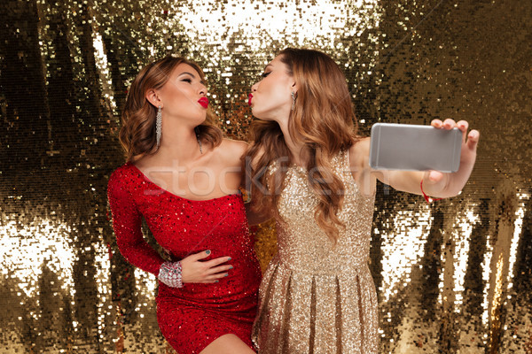 Portrait of two attractive young women in sparkly dresses Stock photo © deandrobot
