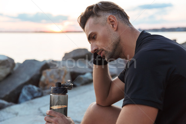 Portrait of a tired sportsman drinking water Stock photo © deandrobot