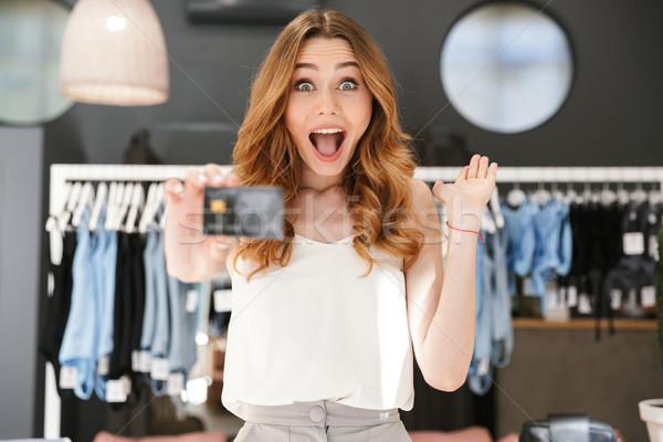 Animado mulher jovem cartão de crédito roupa armazenar Foto stock © deandrobot