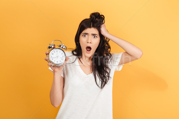 Shocked excited woman holding alarm clock looking camera. Stock photo © deandrobot