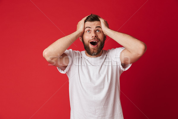 Excited young handsome man looking aside. Stock photo © deandrobot