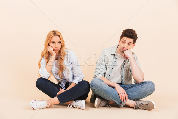 Image of upset man and woman sitting on the floor with in lotus  Stock photo © deandrobot