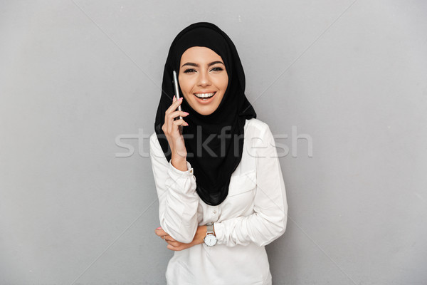 Portrait of happy arabic woman in religious headscarf talking on Stock photo © deandrobot