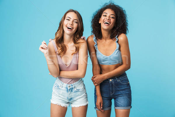 Two laughing young girls dressed in summer clothes Stock photo © deandrobot
