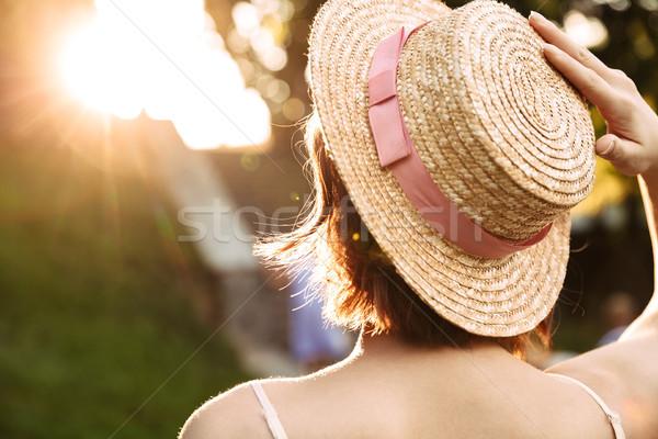 Сток-фото: вид · сзади · женщину · платье · соломенной · шляпе · позируют