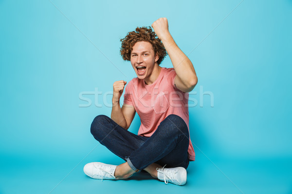 Portrait of a cheerful young curly haired man celebrating Stock photo © deandrobot