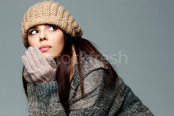 Young pensive woman in warm winter outfit looking away Stock photo © deandrobot