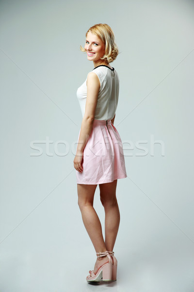 Side view portrait of smiling woman standing on gray background Stock photo © deandrobot
