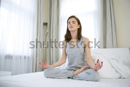 Beautiful woman doing yoga exercises on the bed at home Stock photo © deandrobot