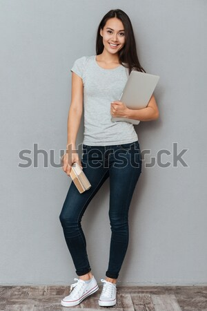 Full length portrait of a happy woman showing blank laptop screen Stock photo © deandrobot