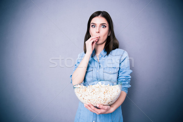 Maravilhado bela mulher alimentação pipoca cinza olhando Foto stock © deandrobot