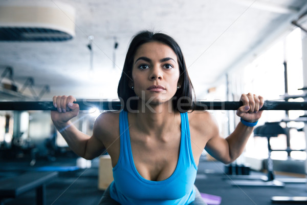 Stock photo: Attractive young woman working out with barbell