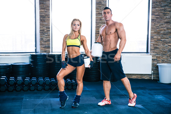 Man and woman holding container with protein at gym Stock photo © deandrobot