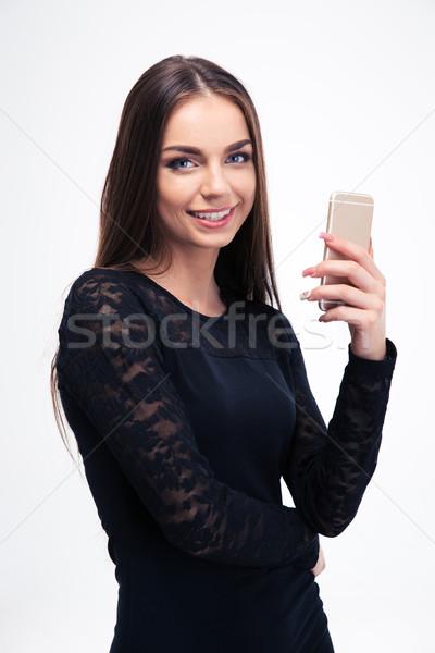 Woman in trendy black dress using smartphone Stock photo © deandrobot