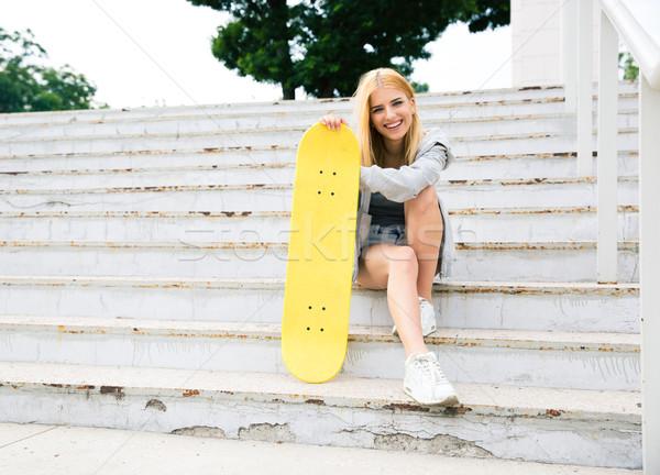 Fiatal lány ül lépcsősor gördeszka boldog park Stock fotó © deandrobot