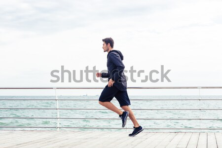 Sports man running near sea Stock photo © deandrobot