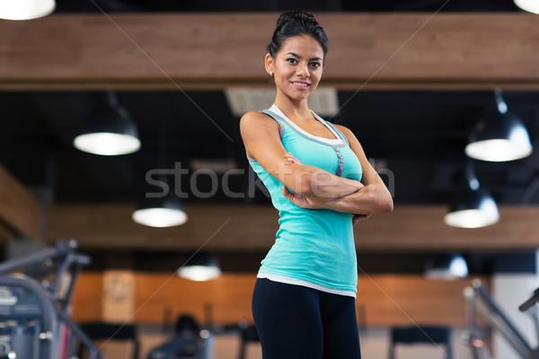 Deportes mujer pie armas doblado gimnasio Foto stock © deandrobot