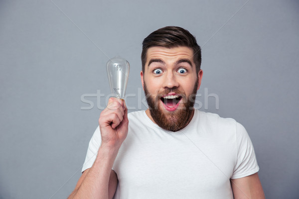 Portrait of a cheerful man holding bulb Stock photo © deandrobot