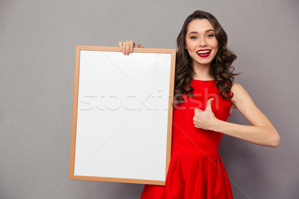 Woman holding blank board and showing thumb up Stock photo © deandrobot