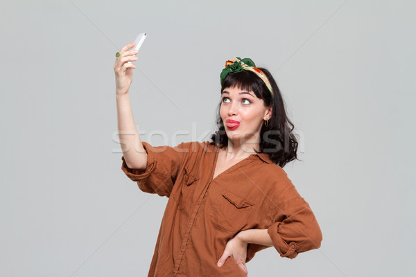 Amusing joyful woman making selfie and showing tongue using smartphone  Stock photo © deandrobot