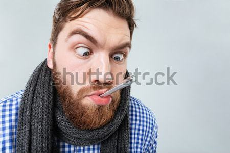 Crazy man joking and grimacing over black background Stock photo © deandrobot
