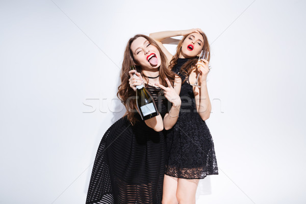Women in night dress drinking champagne and showing tonque Stock photo © deandrobot