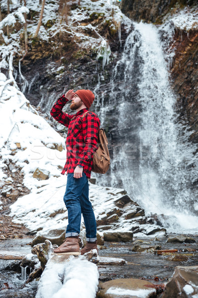 Handsome berded man walking near waterfall at mountains in winter Stock photo © deandrobot
