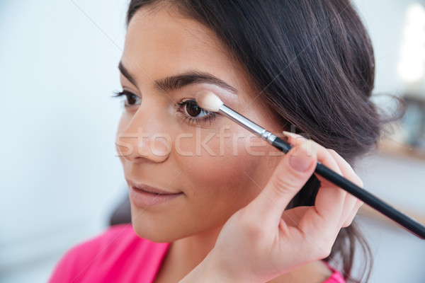 Makeup artist applying eyeshadow to attractive woman  Stock photo © deandrobot