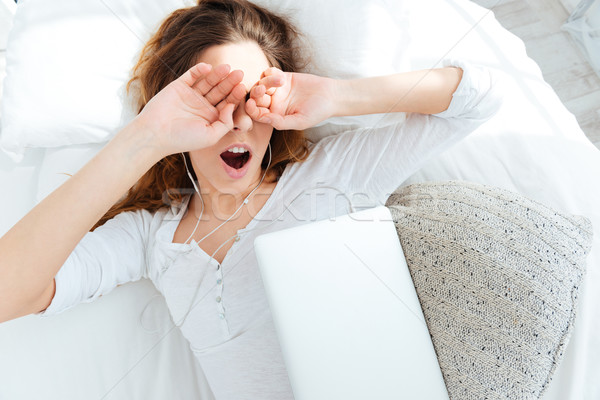 Woman waking up and rubbing her eyes Stock photo © deandrobot