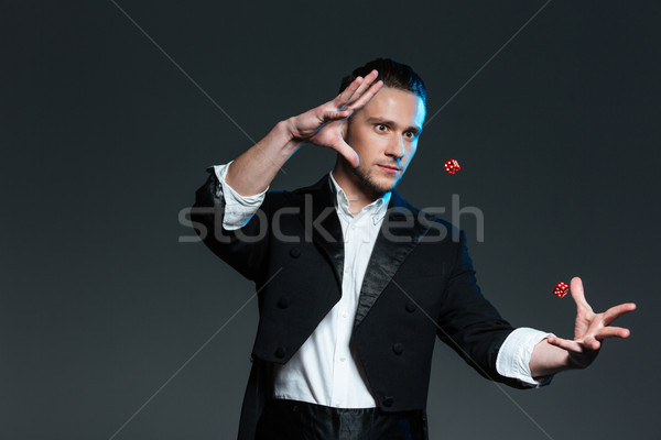 Handsome young man magician showing tricks with flying dice Stock photo © deandrobot