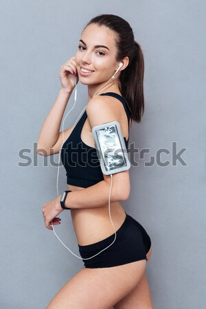 Beautiful young sportswoman using pc tablet over a grey background Stock photo © deandrobot