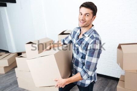 Happy man moving in and carrying carton boxes Stock photo © deandrobot