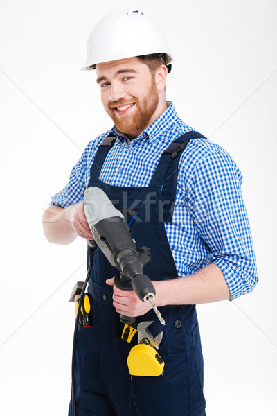 Stock photo: Happy bearded young man in helmet smiling and holding drill
