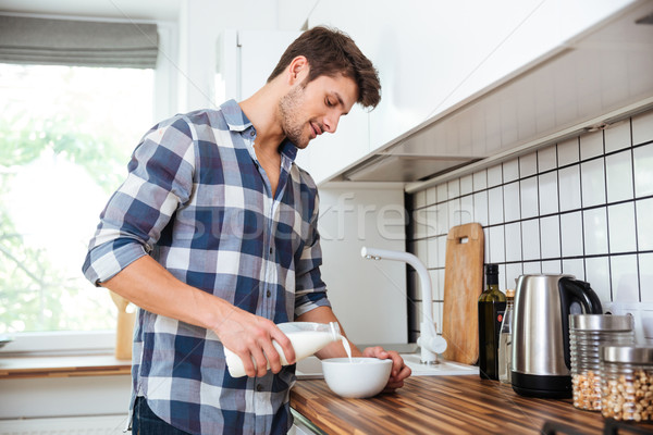 Man pouring milk into bowl for breakfast on the kitchen Stock photo © deandrobot