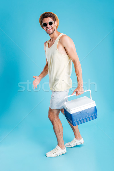 Smiling young man walking and holding cooler bag Stock photo © deandrobot