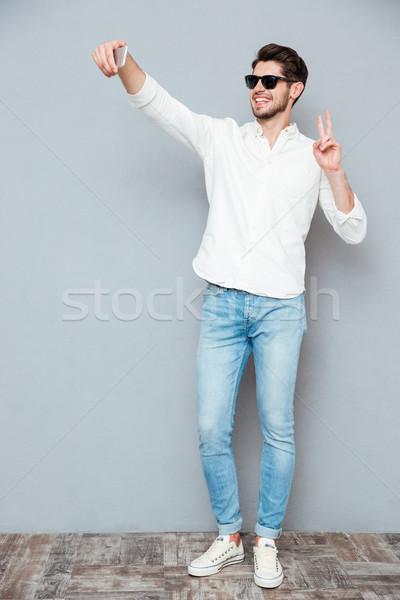 Stockfoto: Gelukkig · jonge · man · zonnebril · smartphone · grijs