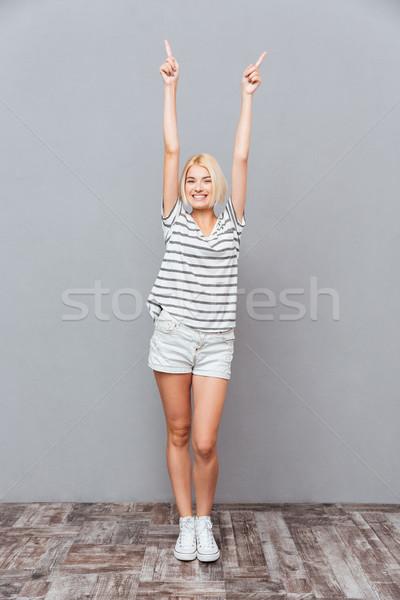 Sorridente mulher jovem em pé indicação para cima tanto Foto stock © deandrobot