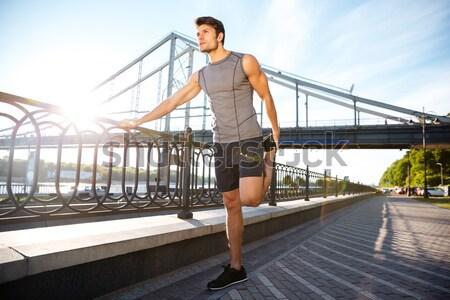 Handsome sports man running along modern bridge at sunset light Stock photo © deandrobot