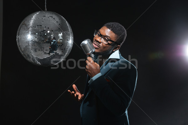 Stock photo: Afro amerian man singing into vintage microphone