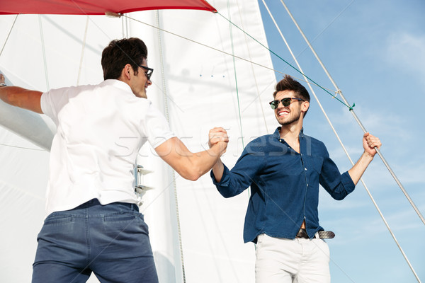 Two young handsome men greeting standing on the yacht Stock photo © deandrobot
