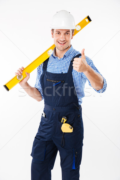 Smiling male builder standing and showing thumbs up gesture Stock photo © deandrobot