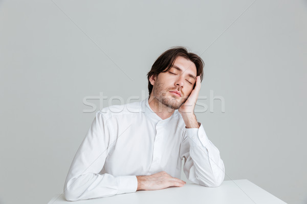 Hadsome young man in white shirt sleeping at the desk Stock photo © deandrobot