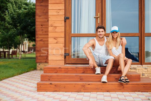 Pár ül ölel veranda ház boldog Stock fotó © deandrobot