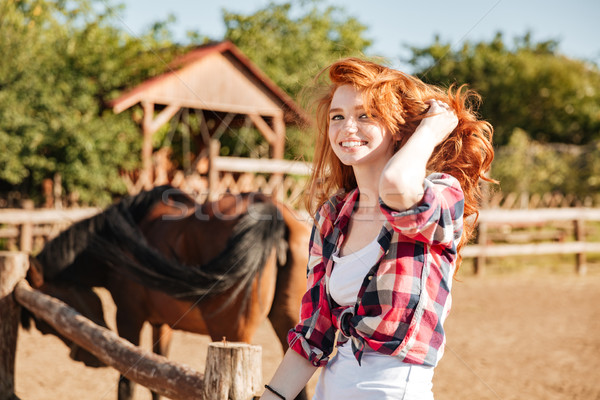 Smiling woman cowgirl with horse sitting on ranch Stock photo © deandrobot