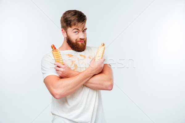 Happy bearded man in filthy shirt holding two hotdogs Stock photo © deandrobot