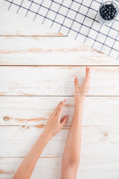 Hands taking glass with blueberries on wooden background Stock photo © deandrobot