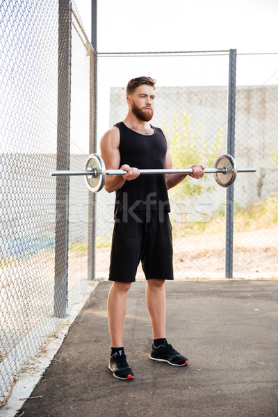 Full length of concentrated man athlete working out with barbell Stock photo © deandrobot