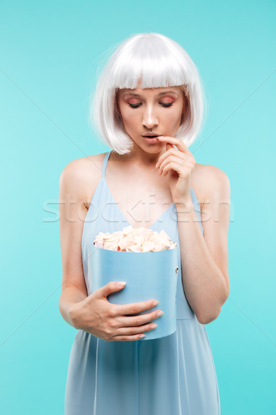 Attractive blonde young woman standing and looking at sweet marshmallows Stock photo © deandrobot